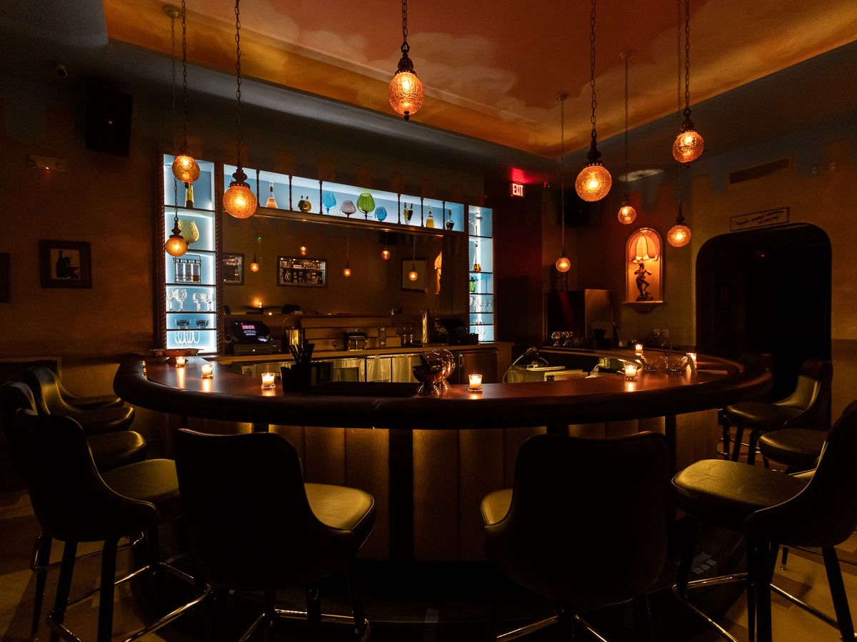 A horseshoe shaped bar with amber pendant lights hanging from the ceiling and a blue back bar.