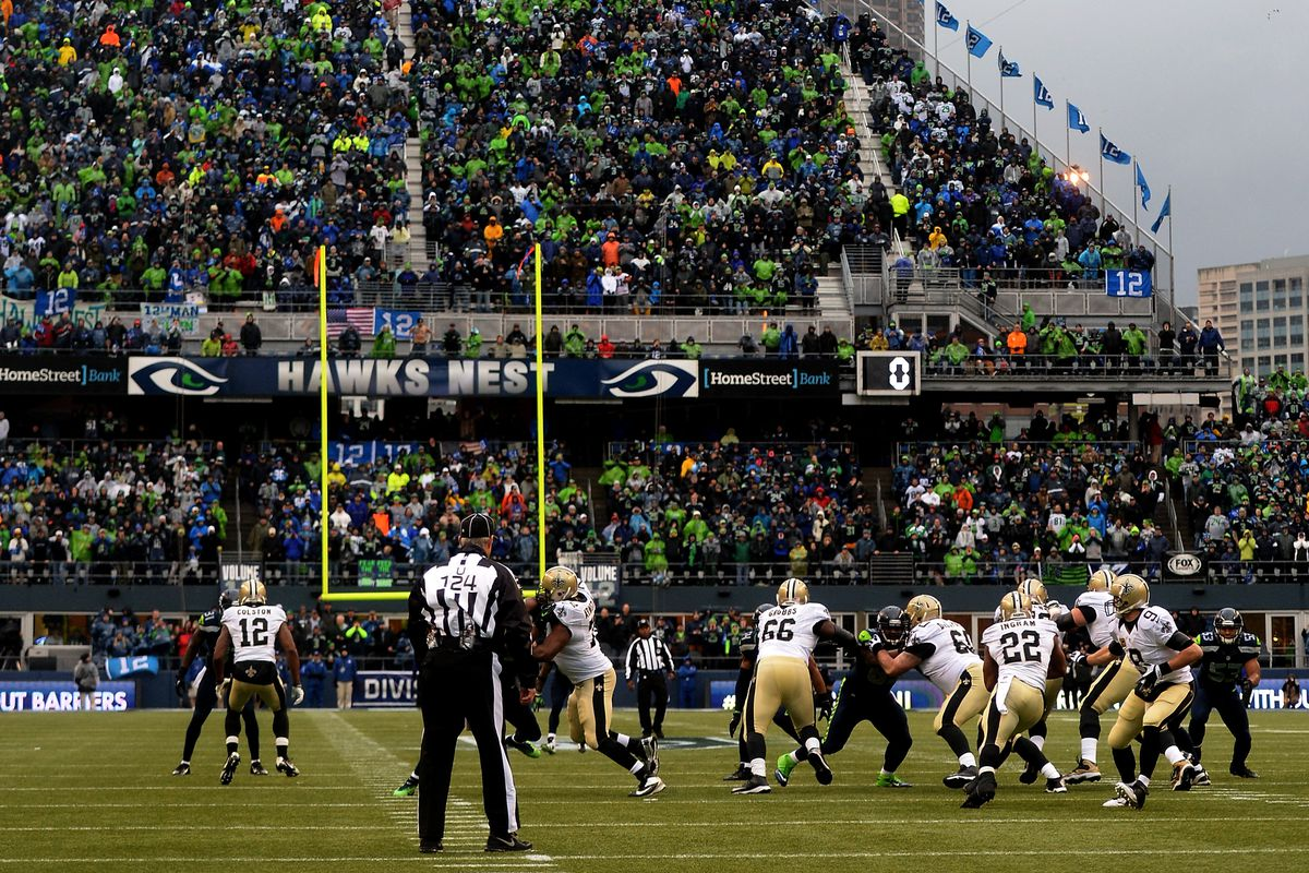 SEATTLE, WA - Quarterback Drew Brees (9) hands the ball off to running back Mark Ingram (22) in the second quarter against the Seattle Seahawks during the 2014 NFC Divisional Playoffs at CenturyLink Field.