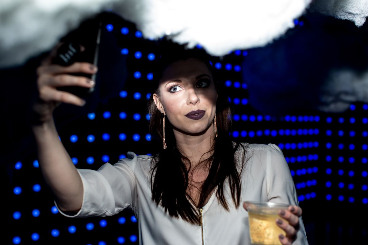 Dream Machine woman taking a selfie with a cloud, blue lights in the background