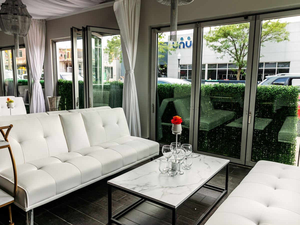Two white sofas face each other with a marble table in the middle. The sofas are close to the front window
