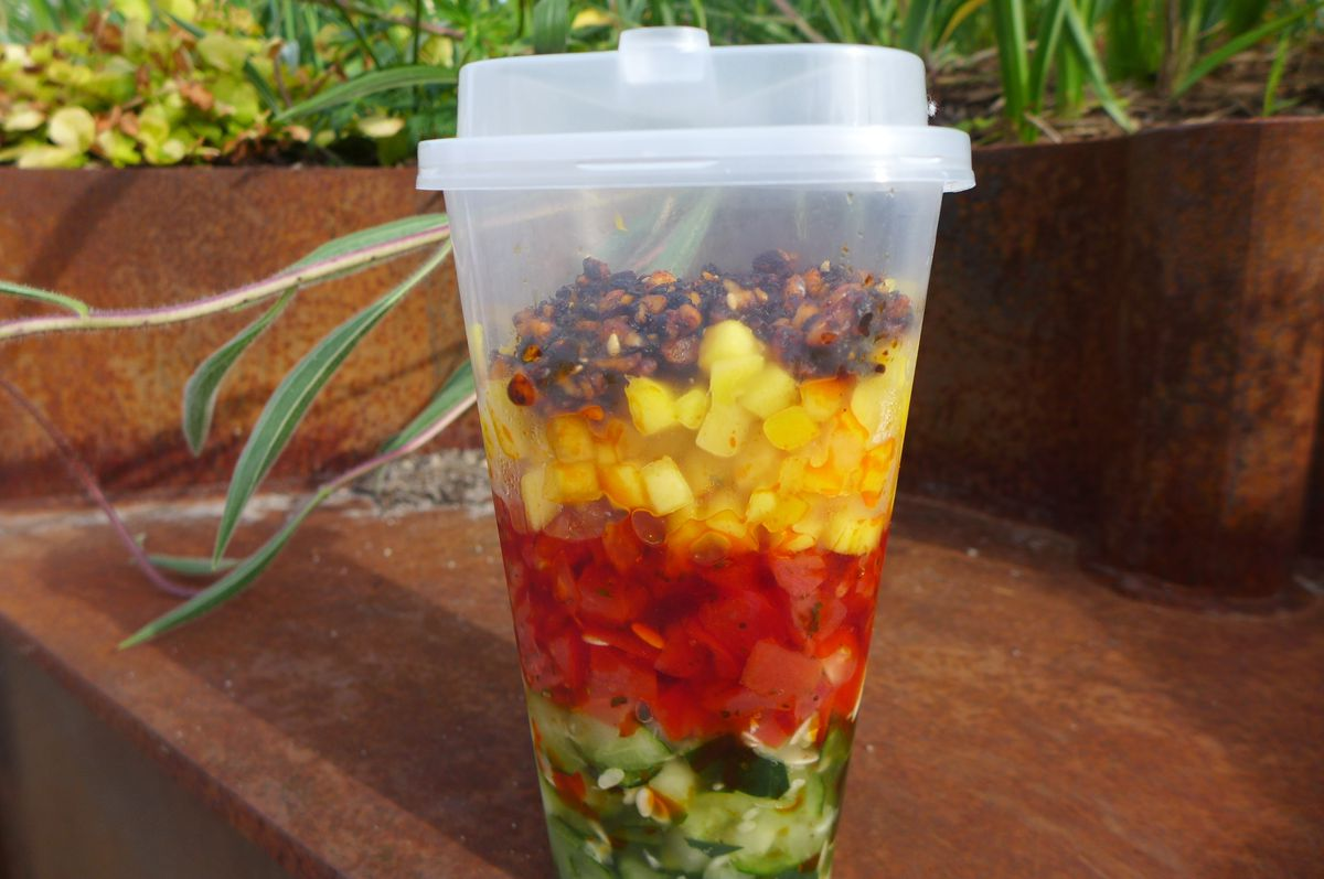 A cup with layers of diced mango, tomato, and cucumber, with a dark crumbly relish on top.