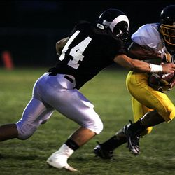 Highland's Alex Olsen tackles Cottonwood's Isi Sofele during a regular season game last year. Olsen is a key returning starter for the Rams heading into the 2009 season.