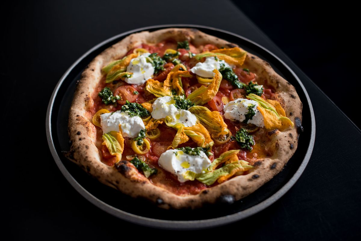 A whole pizza from Pizzana, with burrata and squash blossoms.