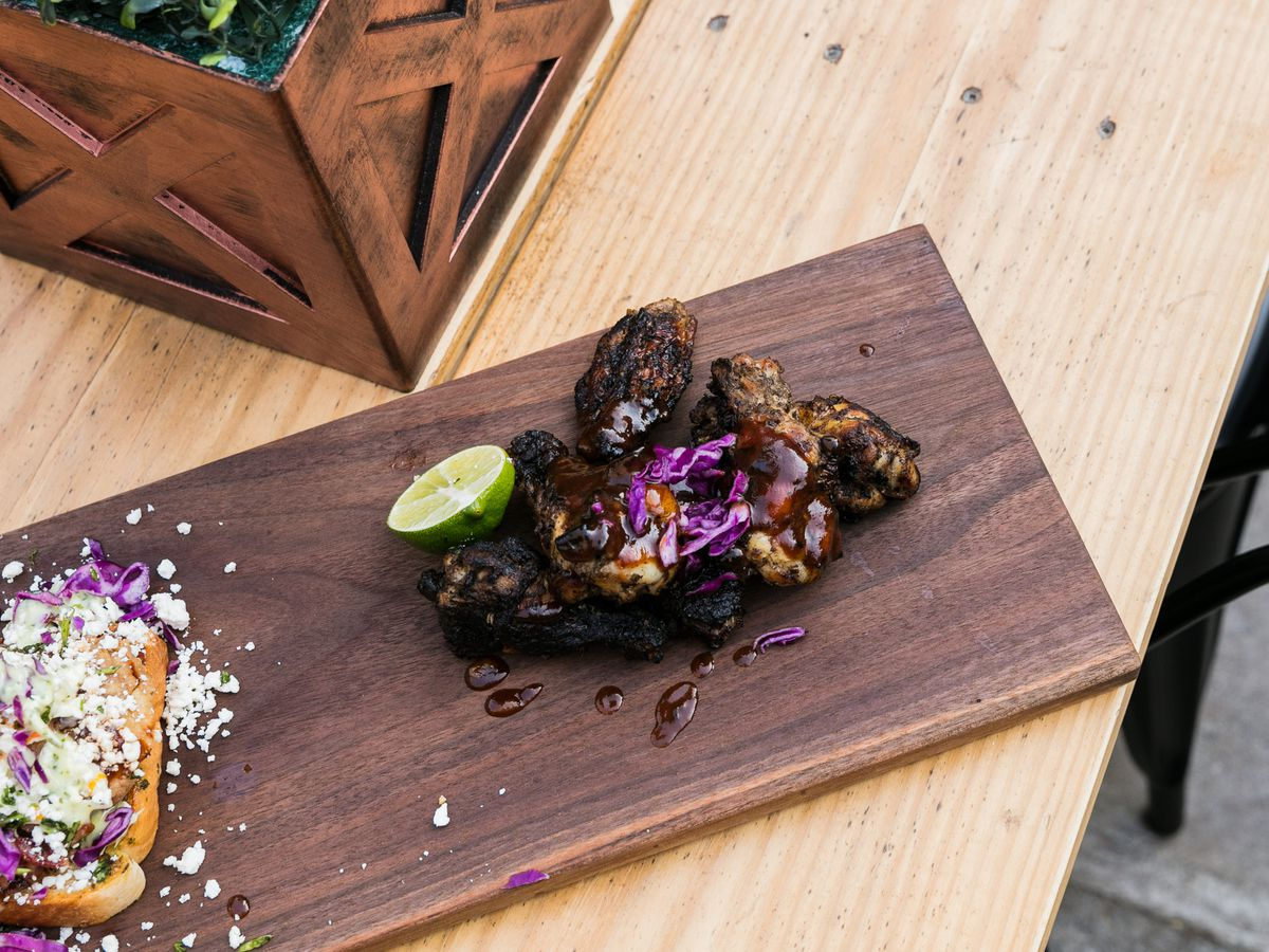 Jerk chicken wings piled on a wood plank with shredded red cabbage and a slice of lime from Coop at Detroit Shipping Company.