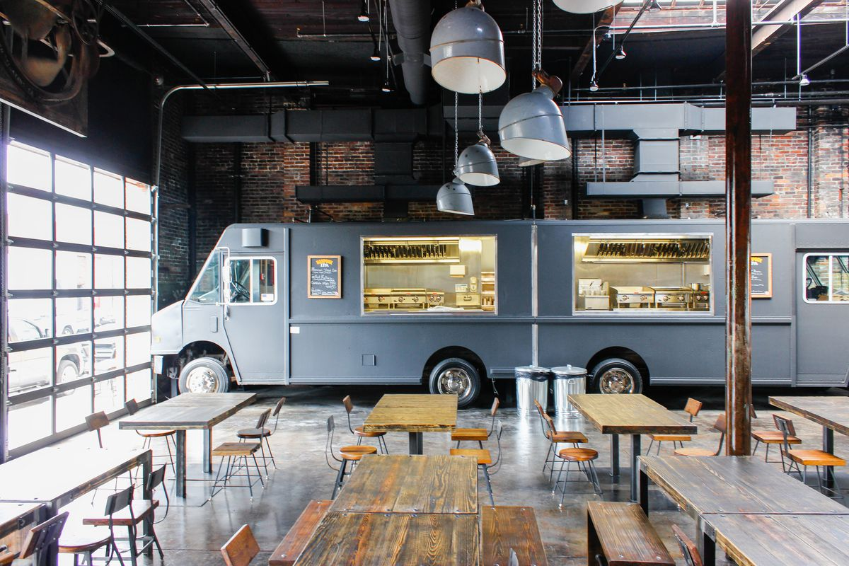 A food truck sits inside of Coppersmith in Boston, which is a bar, restaurant, and event space built into a former copper foundry.