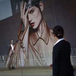 Chinese walks past a luxury advertising board in downtown Beijing, China, Friday, April 13, 2012.  China's economic growth fell to its lowest level in nearly three years in the first quarter but analysts said the economy should rebound in coming months.