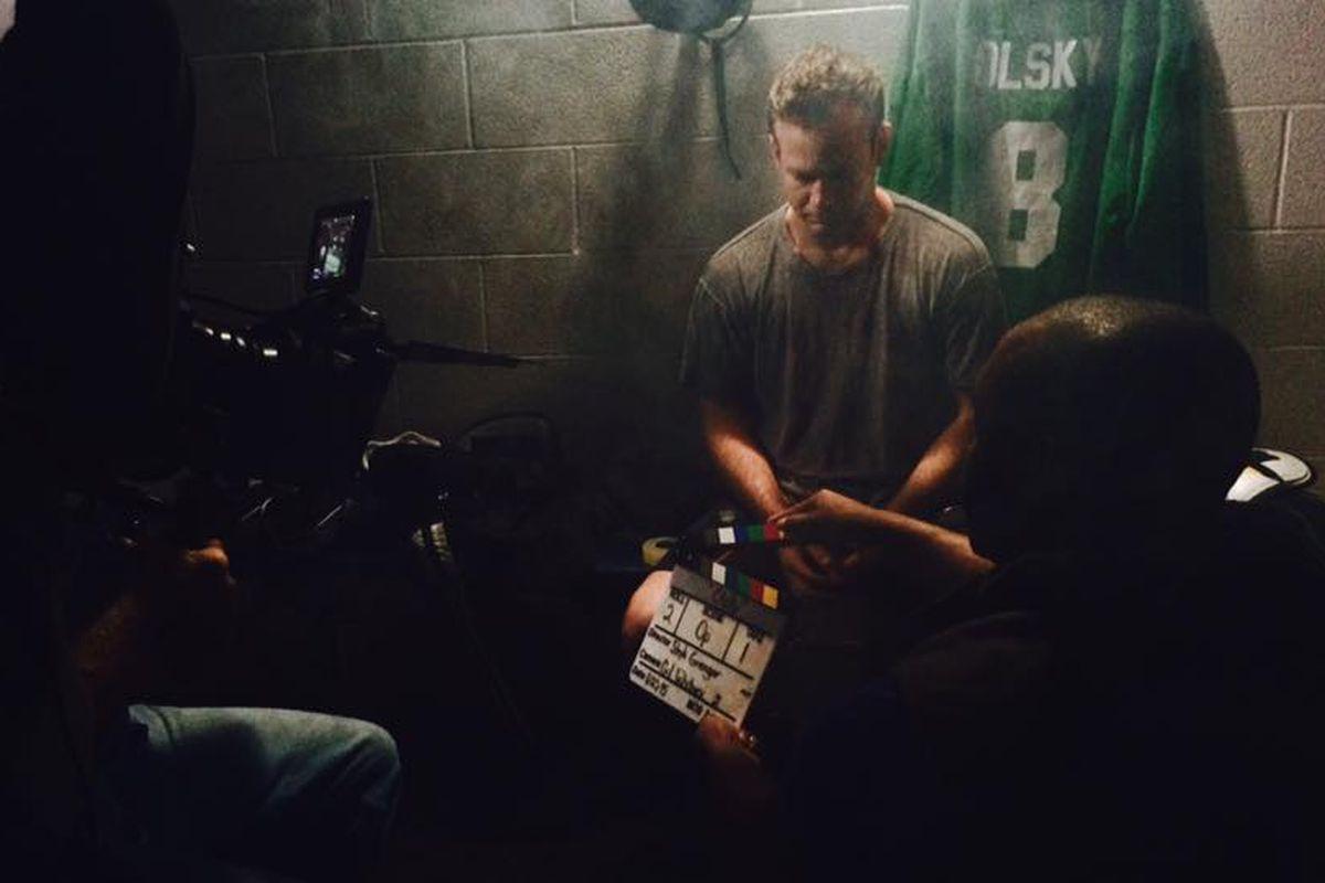 Aaron Massey (Mike Olsky) sits in a darkened locker room as the crew prepares to shoot