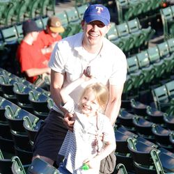 Emilie Parker attends a baseball game with her father, Robbie. Emilie was killed in Friday's school shooting.