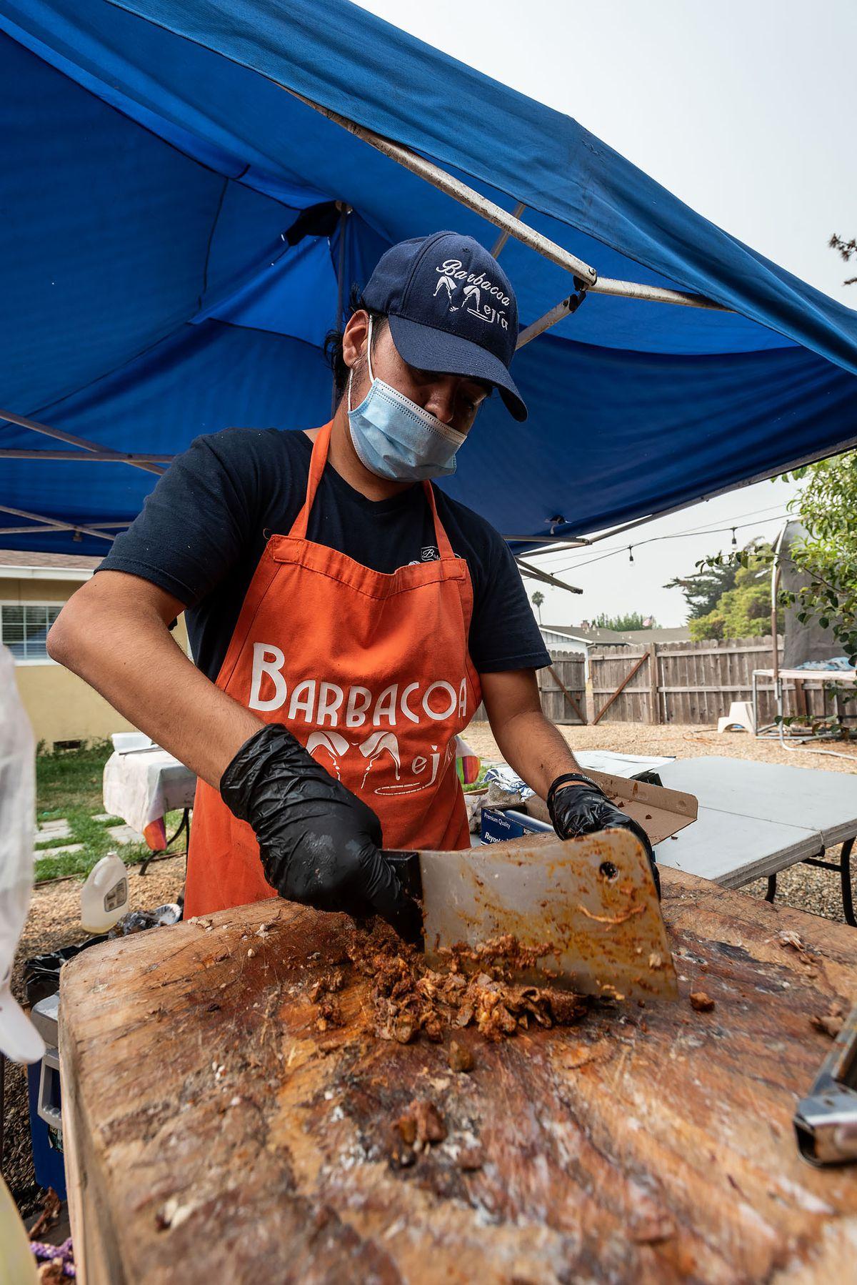 Omar Mejía Jr. chops meat with a butcher's knife.