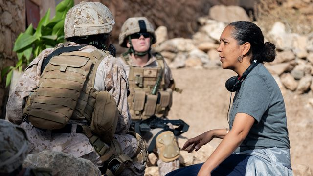 Director Gina Prince-Bythewood talks to extras playing soldiers on the set of The Old Guard.
