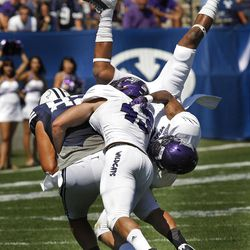Brigham Young Cougars tight end Kaneakua Friel (82) is brought down by Weber State Wildcats cornerback Devin Pugh (3) and Weber State Wildcats linebacker Luke King (43) during the first half as Brigham Young University plays Weber State University in football  Saturday, Sept. 8, 2012, in Provo, Utah.