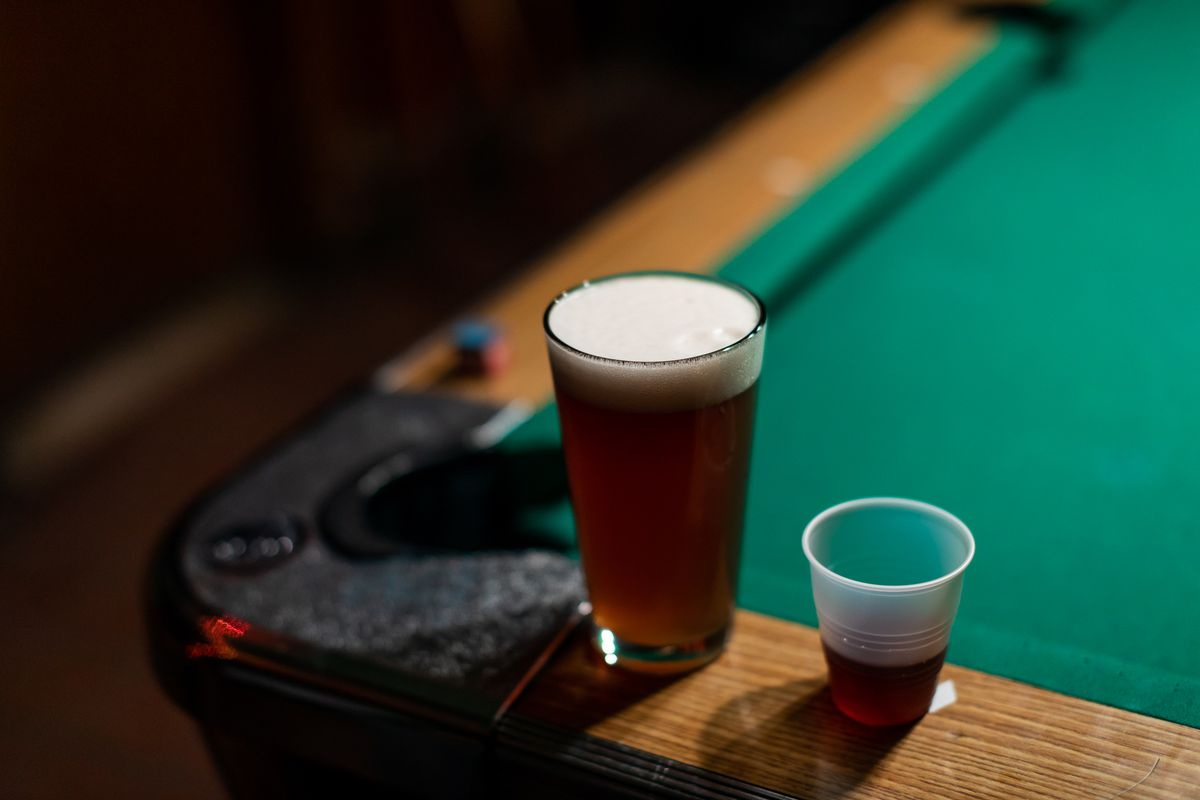 A beer in a pint glass and a shot of Jezy in a plastic cup sit on the corner of the pool table at Whiskey In the Jar.