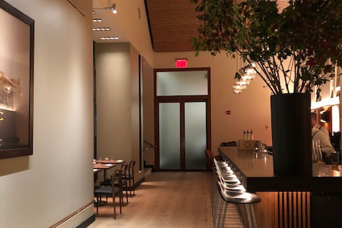 Inside Aquavit, there is a giant potted plant in the foreground, bar stools, wooden floors, and a glass door can be seen in the distance.