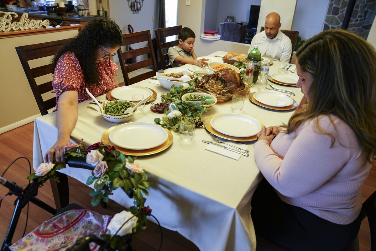Vivian Zayas holds onto the walker once belonging to her recently deceased mother Ana Martinez while her family prays before Thanksgiving dinner, Thursday, Nov. 26, 2020, in Deer Park, N.Y. Members of President Joe Biden's COVID-19 response team fear herd immunity won't come until Thanksgiving 2021.
