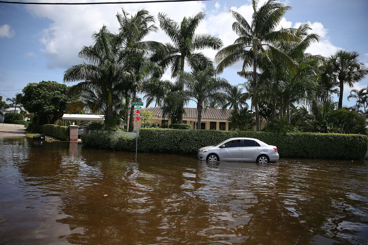 A vehicle drives through flooded streets caused by the combination of the lunar orbit which caused seasonal high tides and what many believe is the rising sea levels due to climate change on September 30, 2015 in Fort Lauderdale, Florida.
