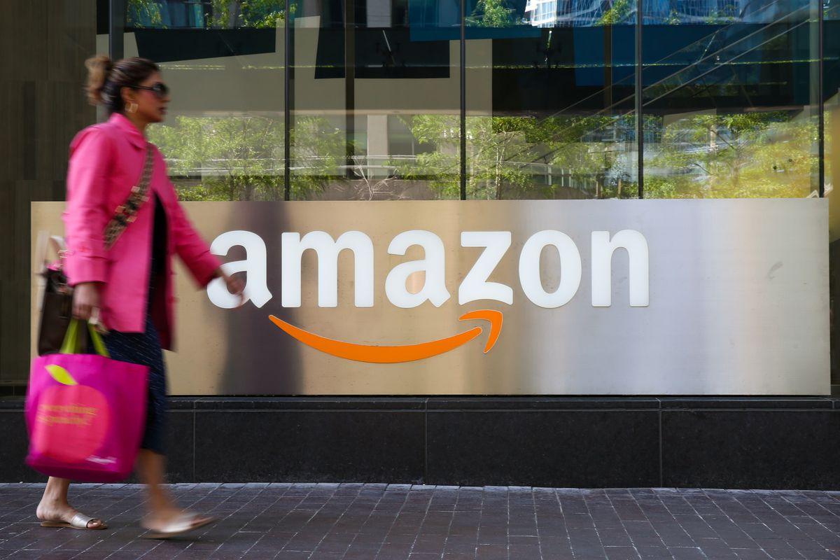 A woman walks past an Amazon logo outside a building.