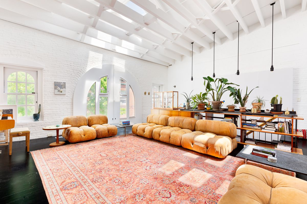 A living area with arched windows, round, brown furniture, planters, and beamed ceilings.