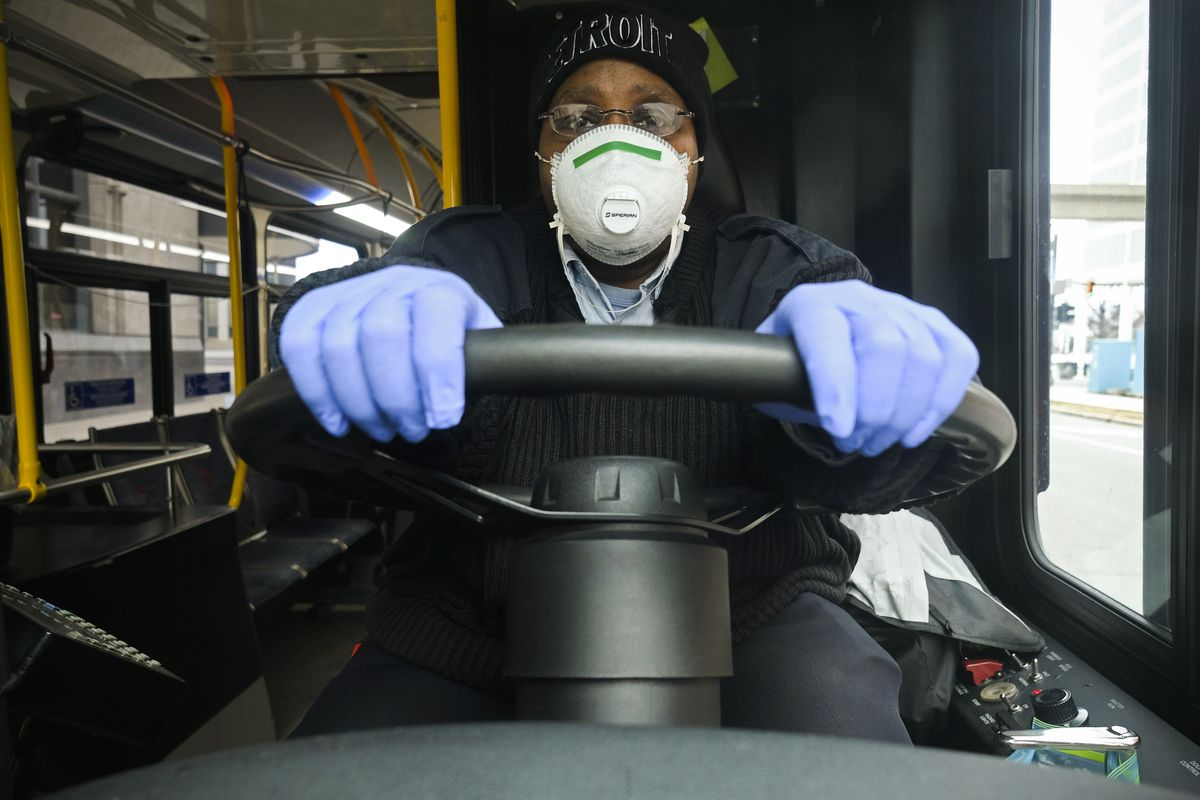 A bus driver sitting in their driver's seat wearing a breathing mask and gloves.