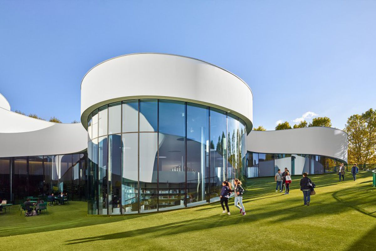 Exterior shot of curving building with facade of white and windows on a sloping site.