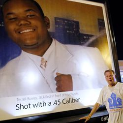 Anti-violence advocate Father Michael Pfleger poses by a picture of a victim of gun violence. | Jim Young/Getty Images