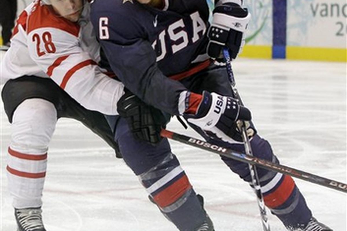 Erik Johnson fights for the puck and was in the middle of the celebration for the Americans' empty net goal that sealed the victory Wednesday against the Swiss.