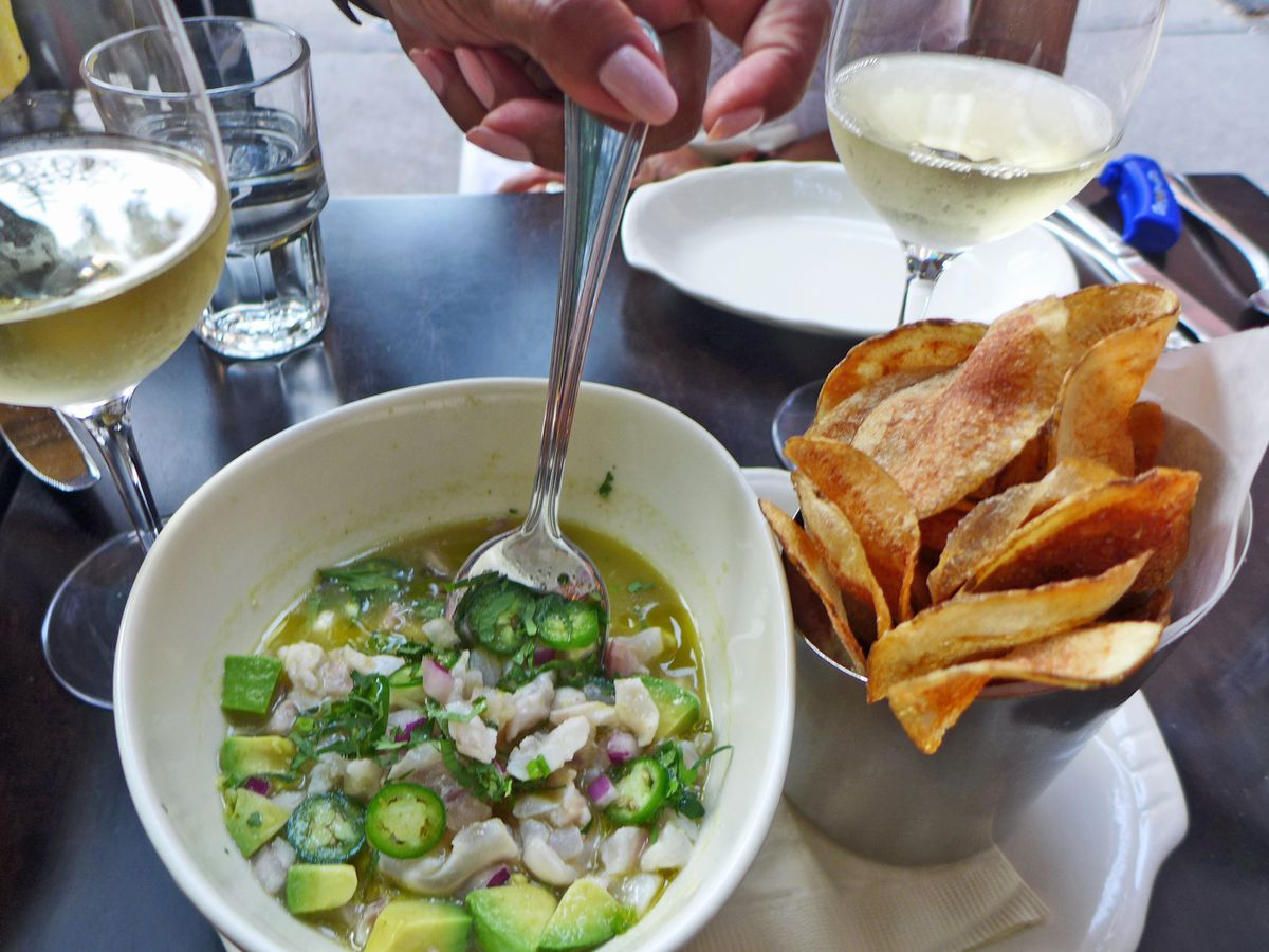 A hand reaches down to scoop up a spoonful of ceviche, with potato chips in a cup at the side.