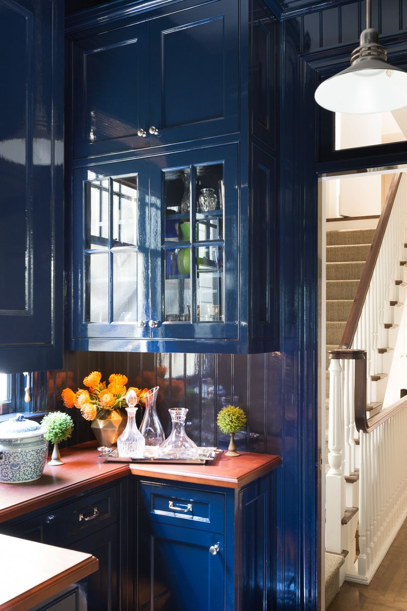 A kitchen with glossy, navy-blue walls.