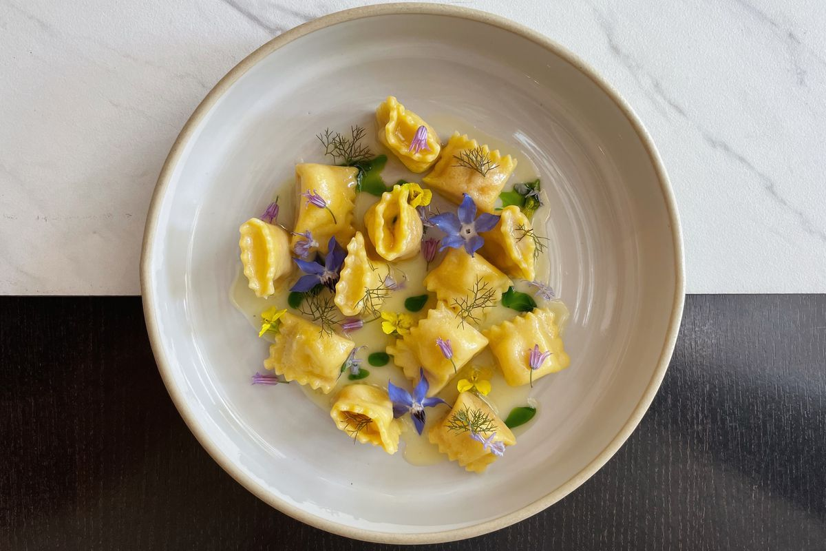Doppio ravioli withcultured butter and foraged purple herbson a white plate, topdown view