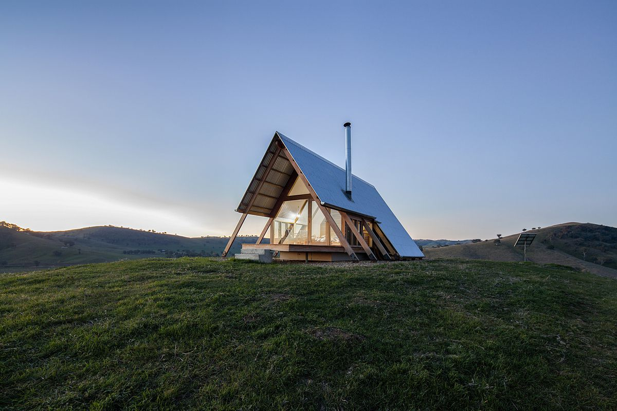 A-frame cabin on grassy hill.