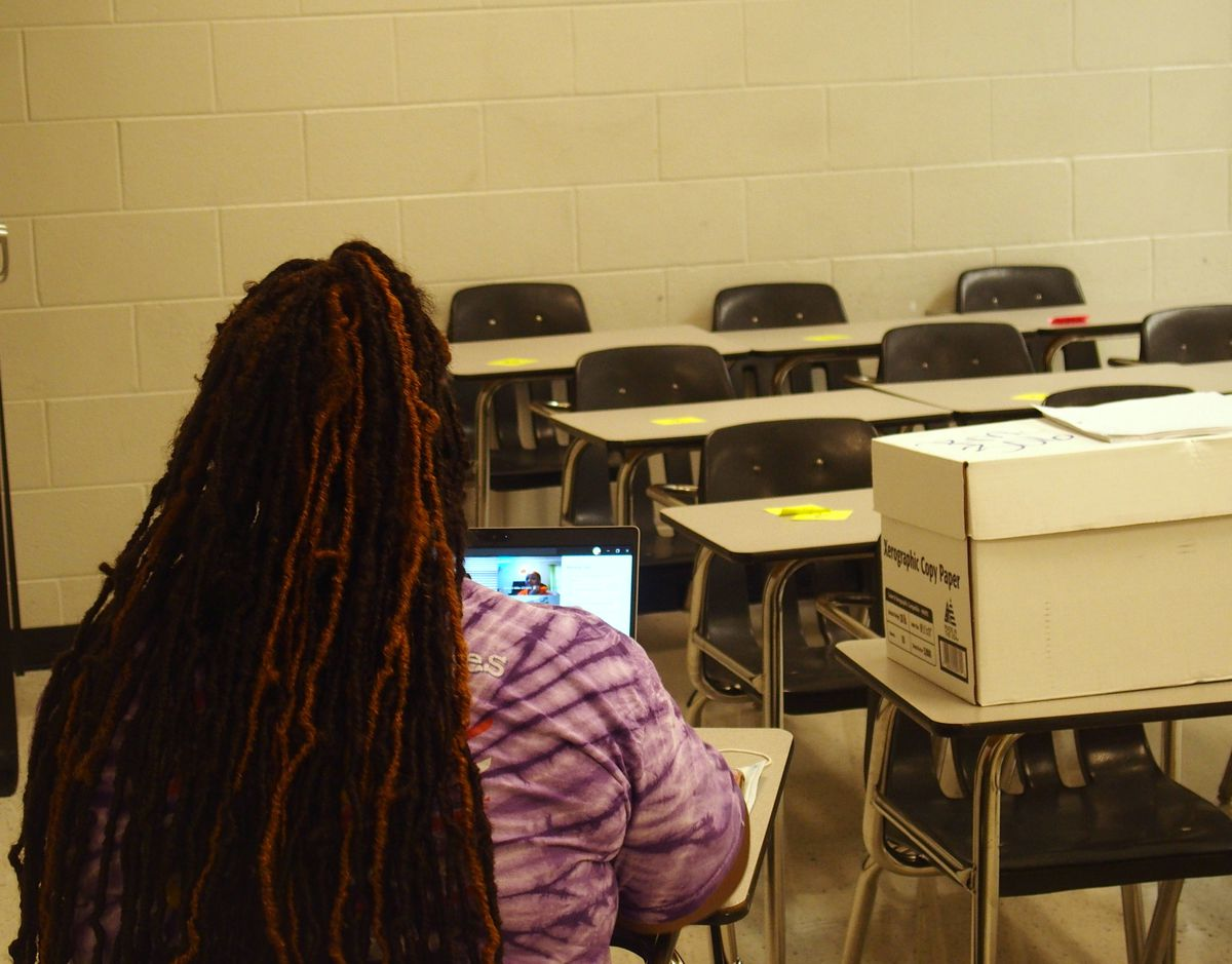 A student participates in an online class in a school building classroom