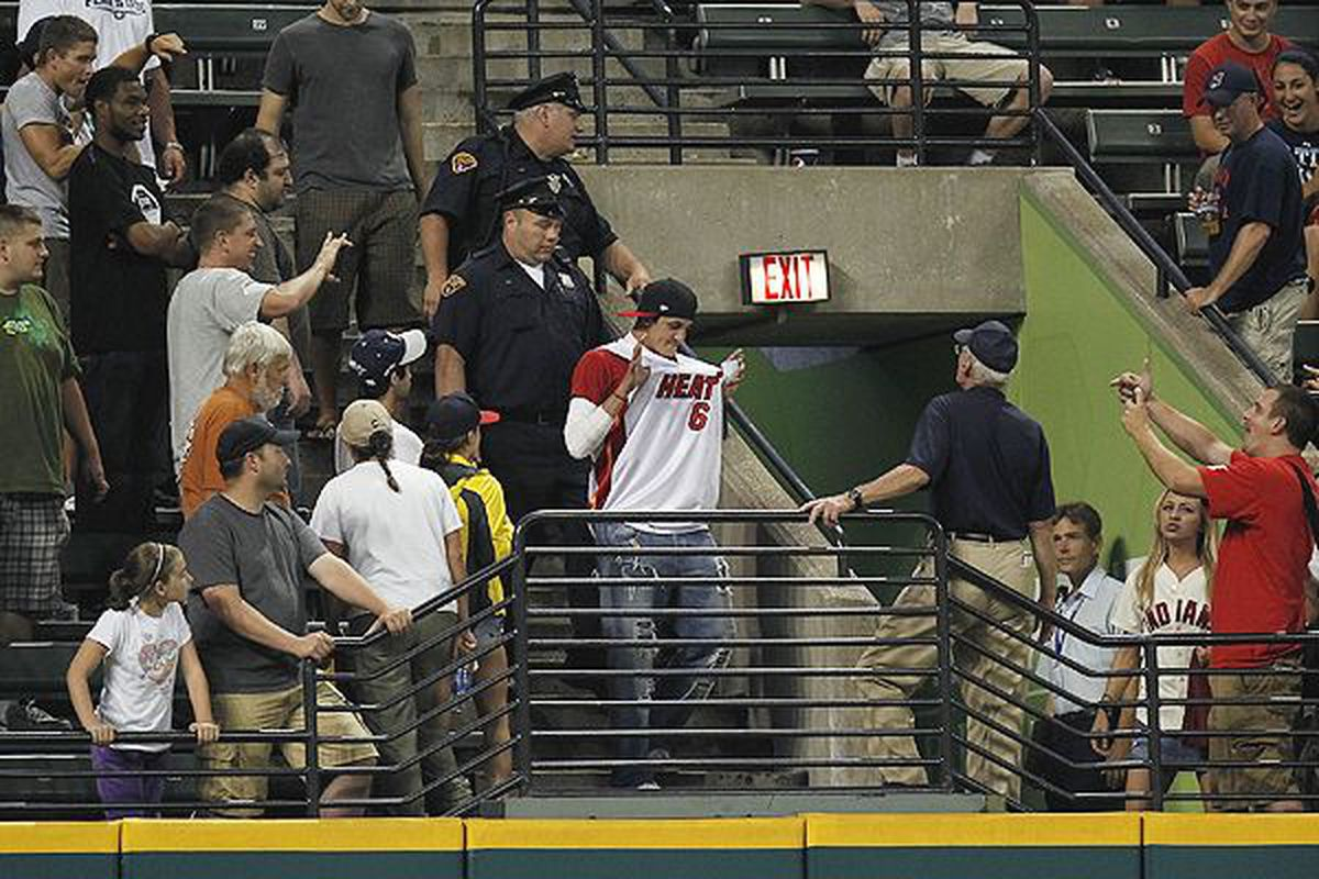 Cleveland Indian fans chant and heckle a spectator wearing a LeBron James Miami Heat Jersey.