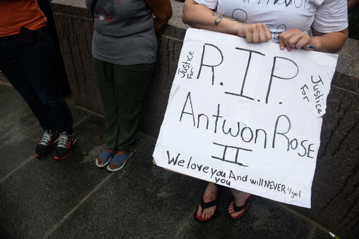 A woman holds a sign during a June 23 protest following the police shooting of 17 year-old Antwon Rose in East Pittsburgh, Pennsylvania.