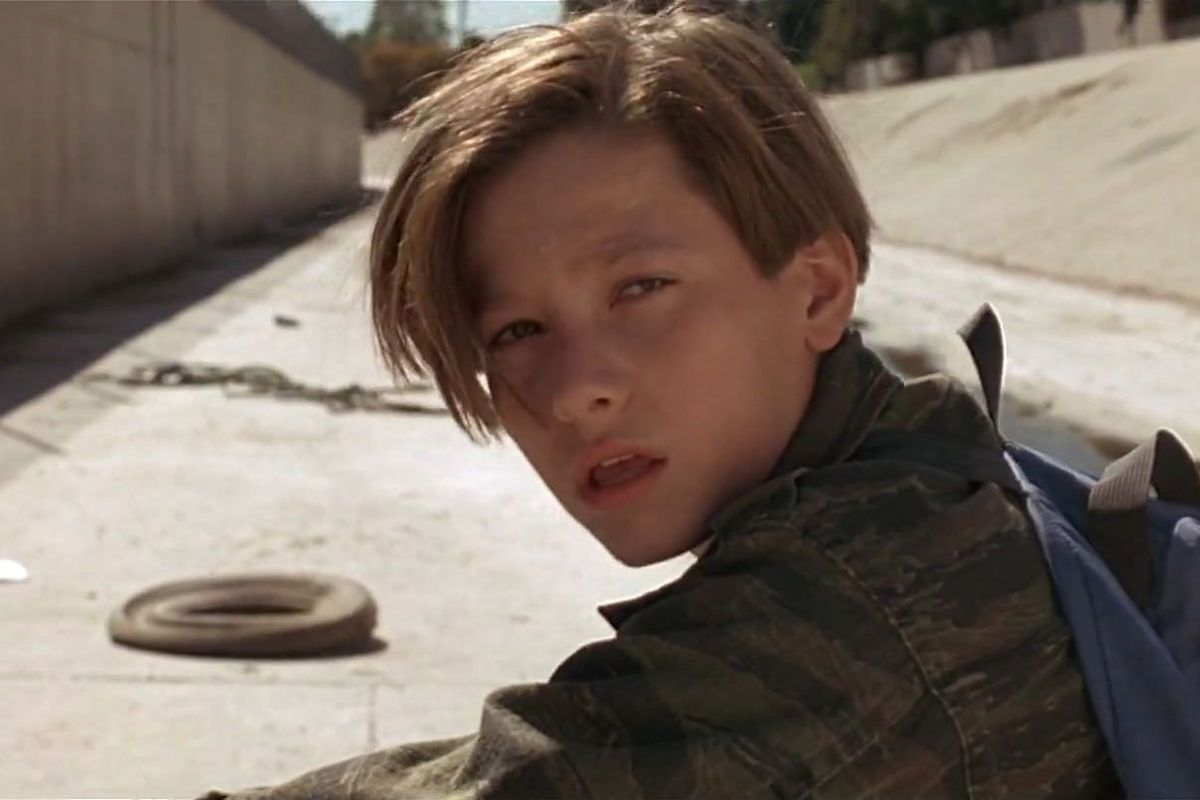 terminator judgment day: john connor stands on his bike looking over his shoulder in the la aqueduct
