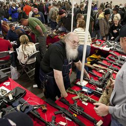 Glen Parshall, center, speaks with an interested seller at the South Towne Expo Center during the 2013 Rocky Mountain Gun Show, Saturday, Jan. 5, 2013.