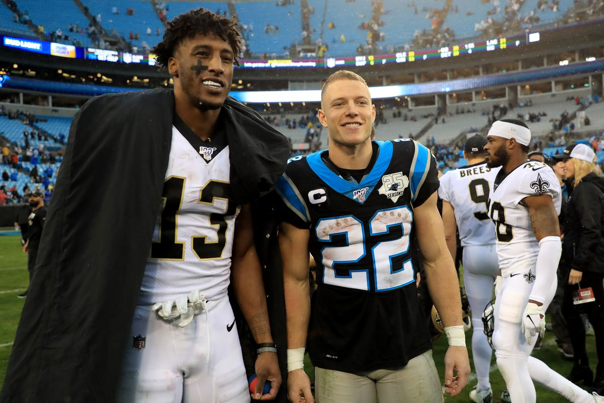 Michael Thomas of the New Orleans Saints poses for a picture with Christian McCaffrey of the Carolina Panthers after their game at Bank of America Stadium on December 29, 2019 in Charlotte, North Carolina.