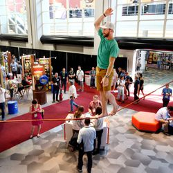 Ryan Robinson performs stunts on a slackline at the Mountain Hardware booth during the Outdoor Retailer Summer Market at the Salt Palace Convention Center in Salt Lake City on Wednesday, Aug. 3, 2016.