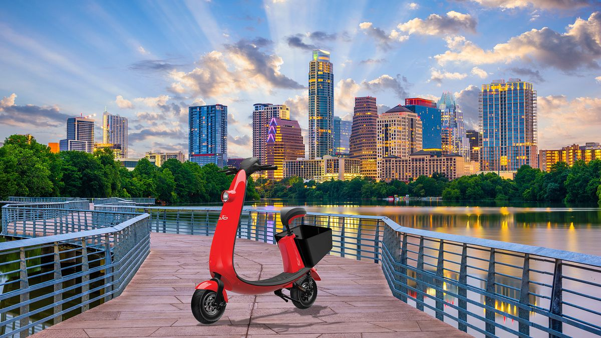 Red scooter in front of Austin skyline