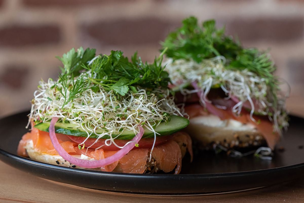 A loaded bagel with lox and sprouts.