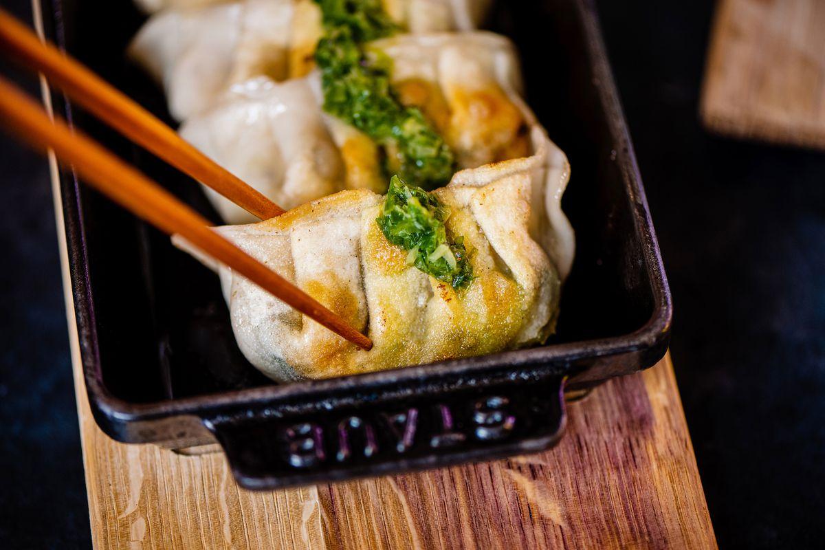 Chopsticks hold pan-fried dumplings up close.