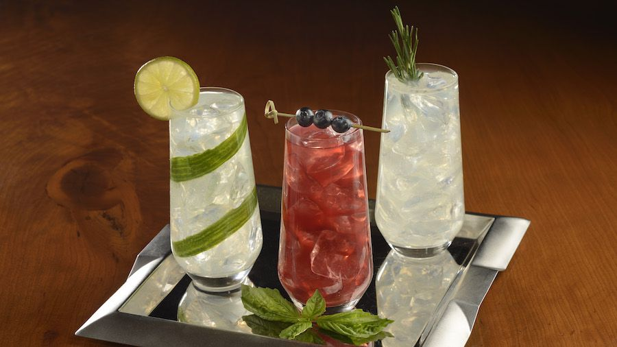 Three highball cocktails, one with cucumber strip and lemon wheel garnish, one bright red with skewered blueberries, and one fizzy with a sprig of thyme, all placed on a silver tray