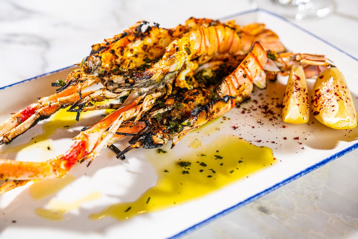 A seafood starter features big prawns surrounded by lemon.