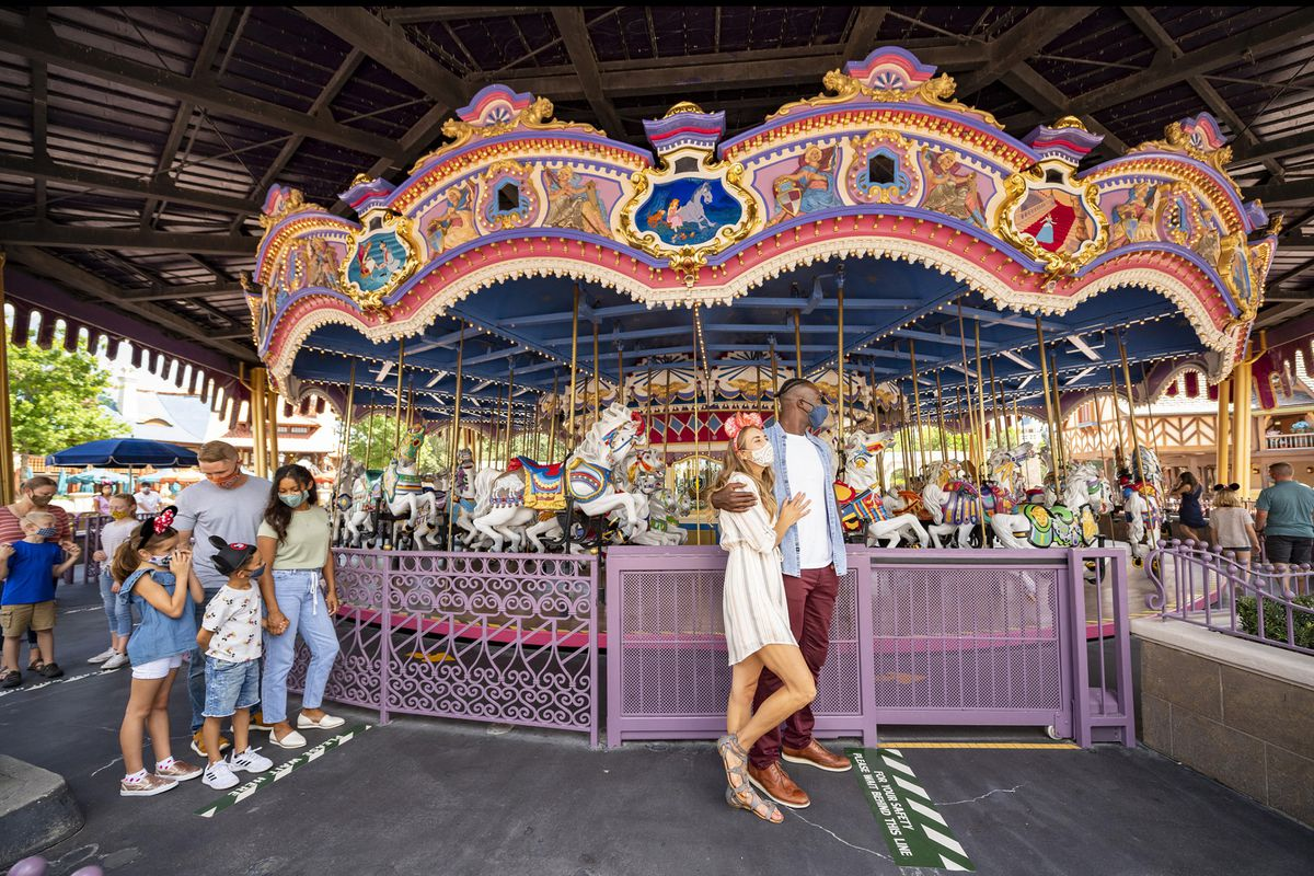 Two families stand outside a merry go round.