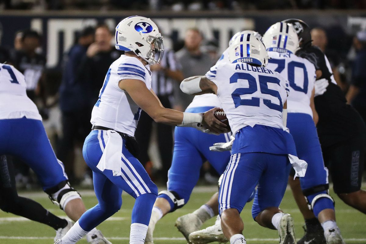 Brigham Young Cougars quarterback Jacob Conover (17) hands off to Brigham Young Cougars running back Tyler Allgeier in Logan on Friday, Oct. 1, 2021.