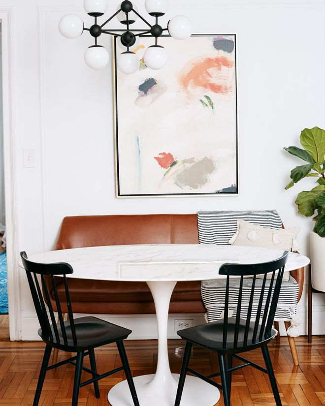 Round white table with black chairs and brown leather bench.