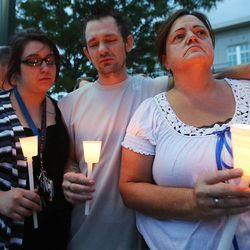 Sgt. Derek Johnson's Aunt Sherrie Bowman, right, and her son Nick and friend Alex Wyker hold candles during a vigil is held in his honor in Draper Sunday, Sept. 1, 2013. Johnson was shot and killed this morning.