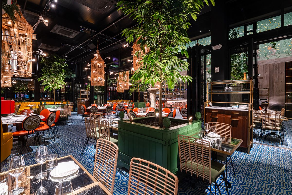 Ilili's soaring dining room is dotted with lots of plant life, orange chairs, and tile work.