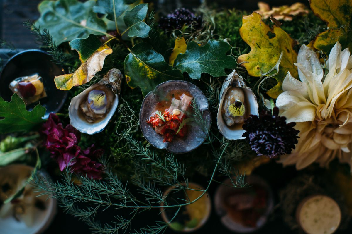 A dish of oysters and accompaniments served on a bed of flowers