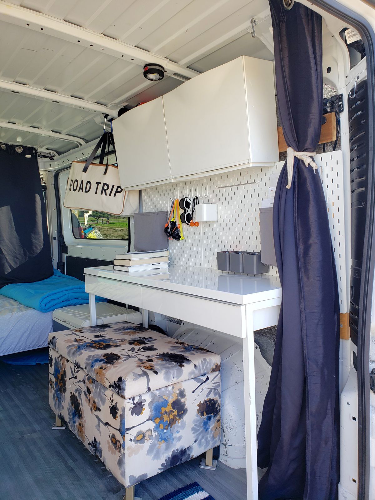 An ottoman with white Ikea desk and peg board sits inside a white camper van.