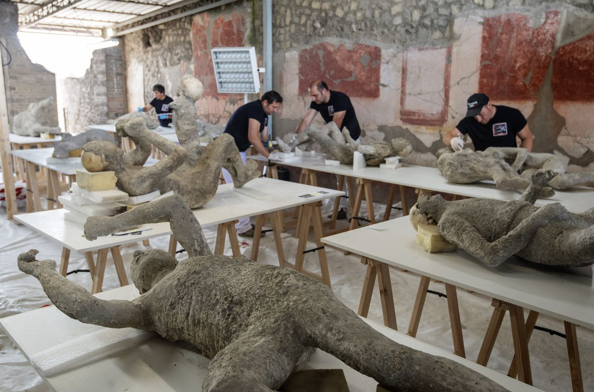 Workers restore casts of victims of the Mount Vesuvius eruption in Pompeii, Italy.
