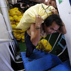 A man carries rice transported on a ferry from Cebu City to Leyte Island in the Philippines, Tuesday, Nov. 19, 2013, following Typhoon Haiyan.
